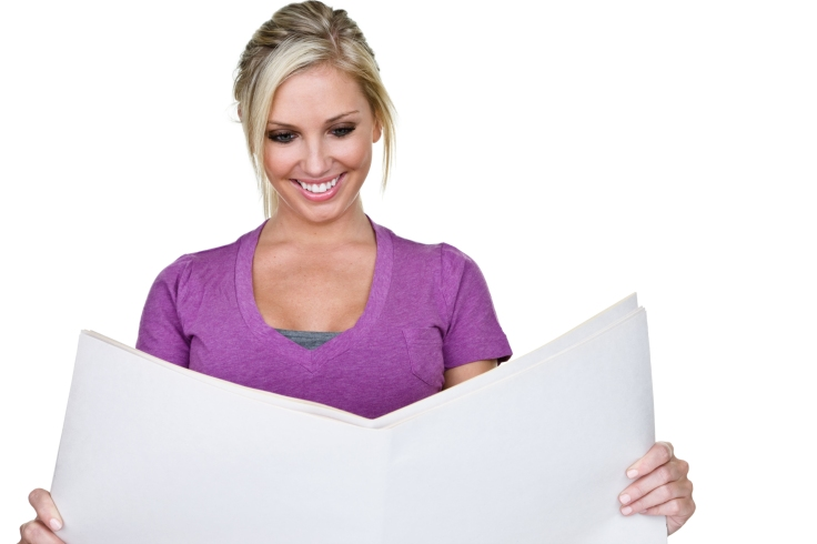 Cheerful woman reading newspaper