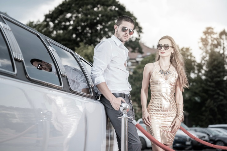 Woman and man leaning against a limo car